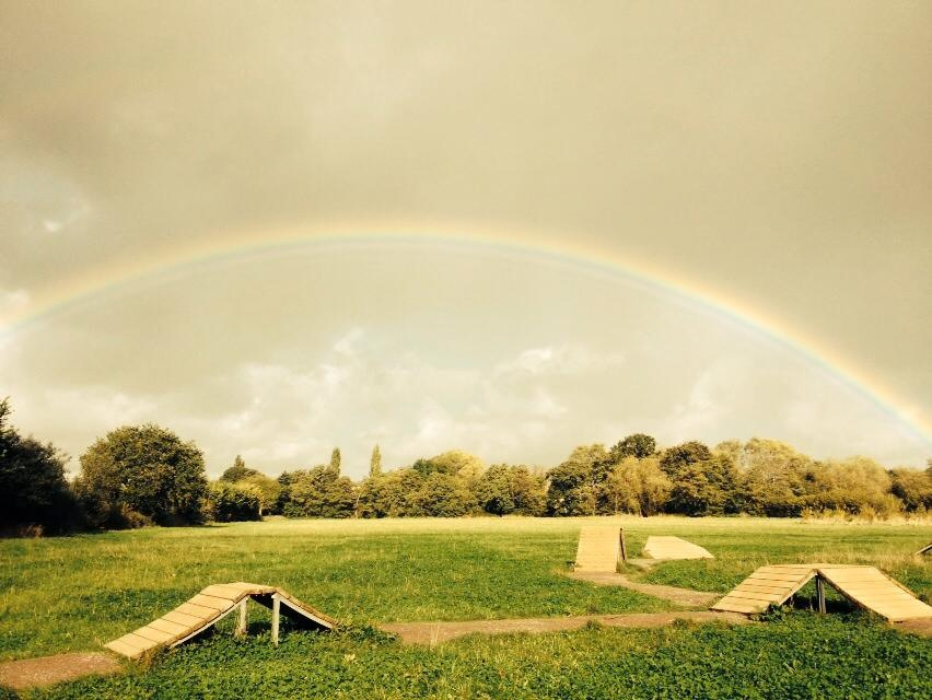 Wooden bike ramps in a field with rainbow in the background