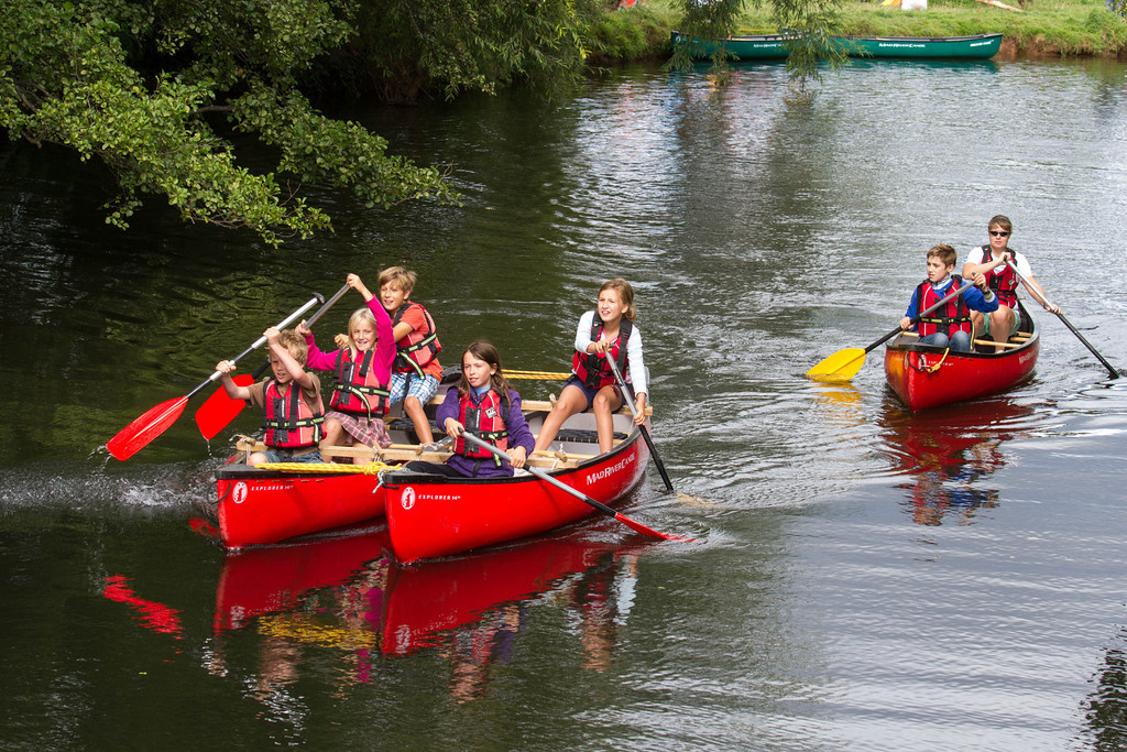 Adults and children paddling canoes on a river