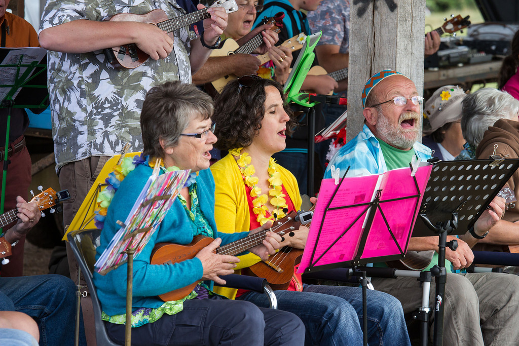 People in brightly coloured clothes singing and playing ukuleles
