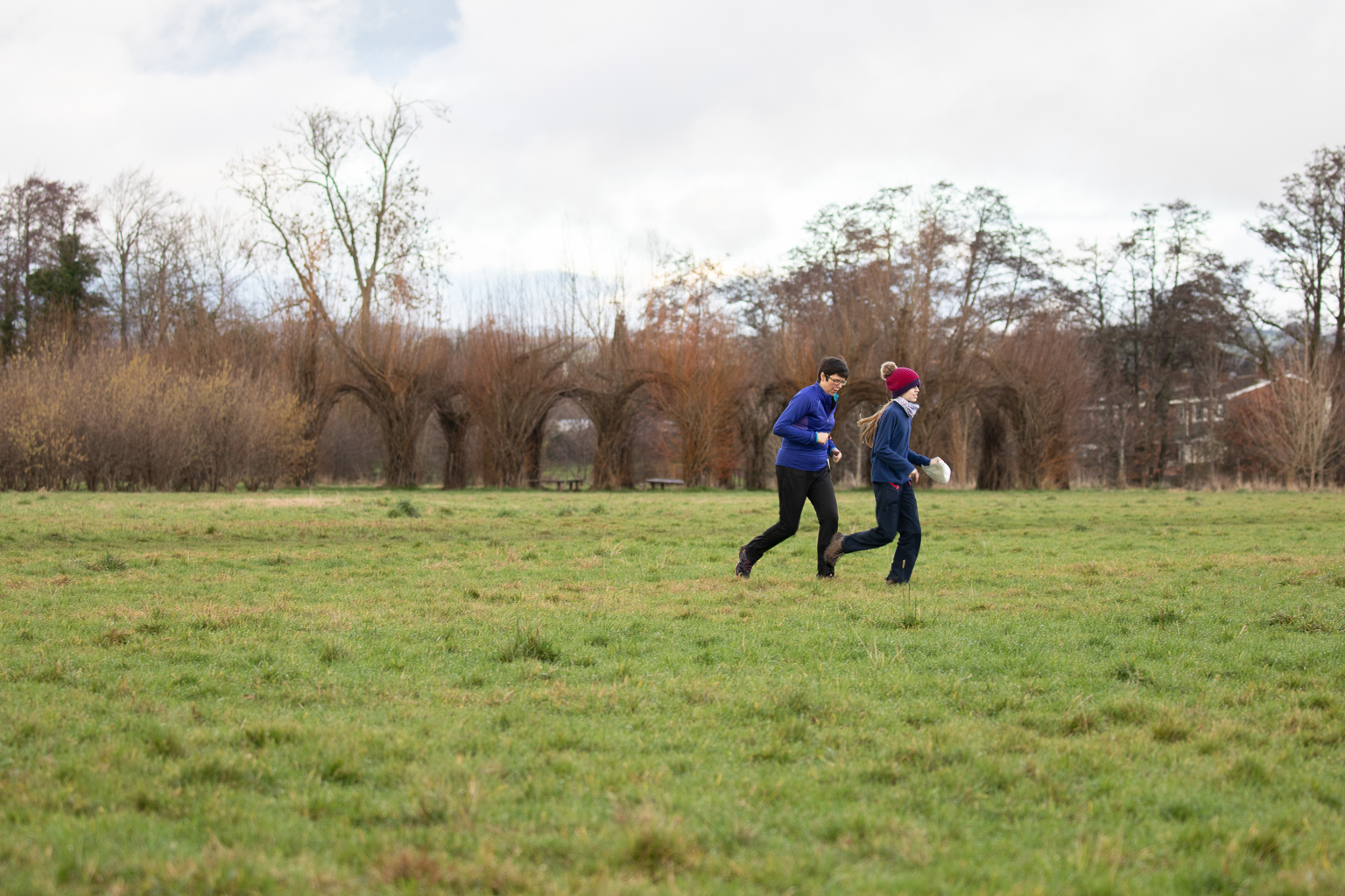 Two people running across a field with piece of paper.