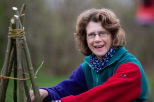 A woman in a colourful fleece jumper working with willow.